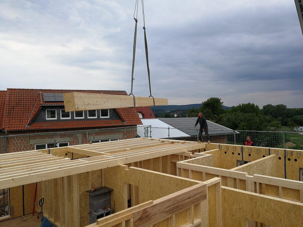 kran mit im Lohnabbund gefertigten Holzelement zum Bau eines Hauses im Holzelementbau